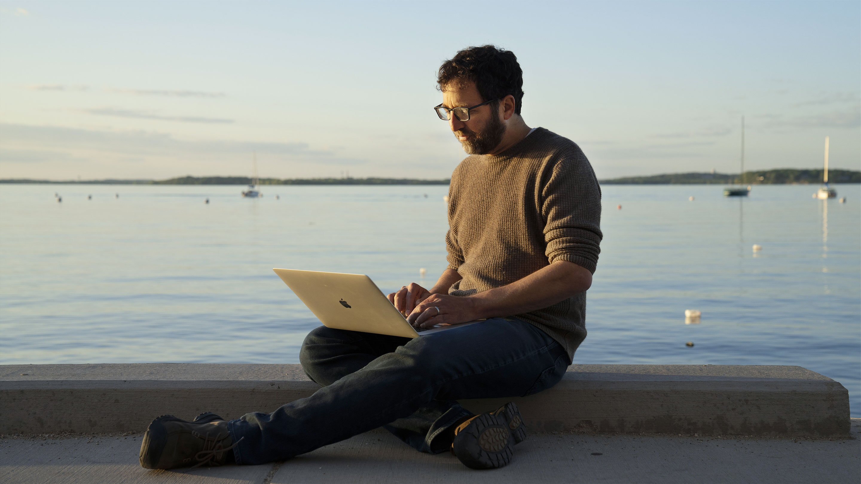 Color photo of Jordan Ellenberg sitting with a laptop by a lake at sunset