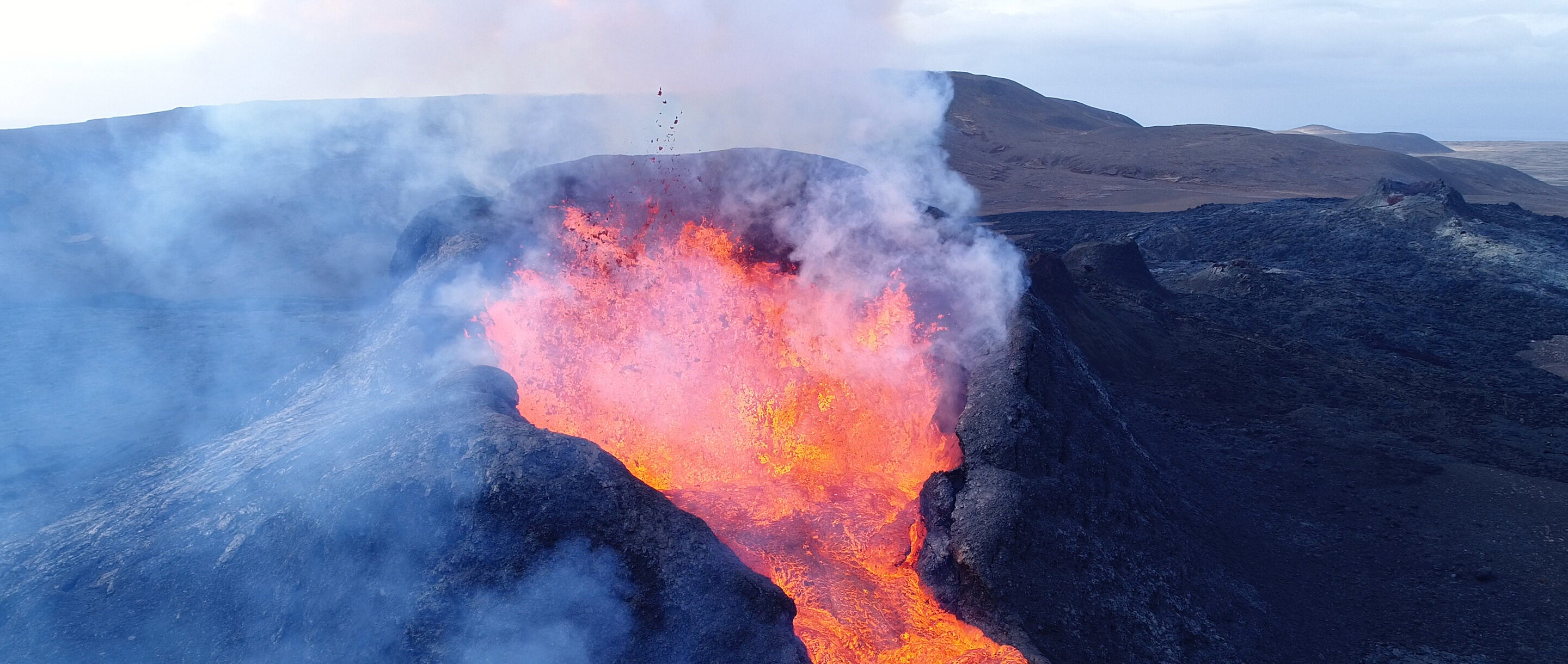 Lava bubbling out of the top of a volcano.