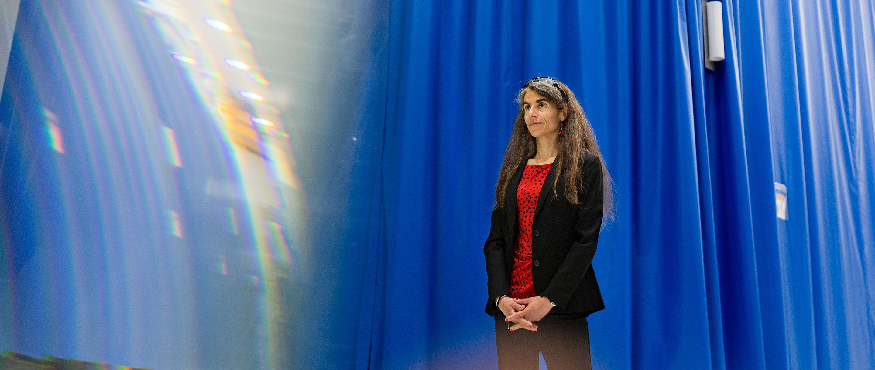 Woman in front of a blue curtain.