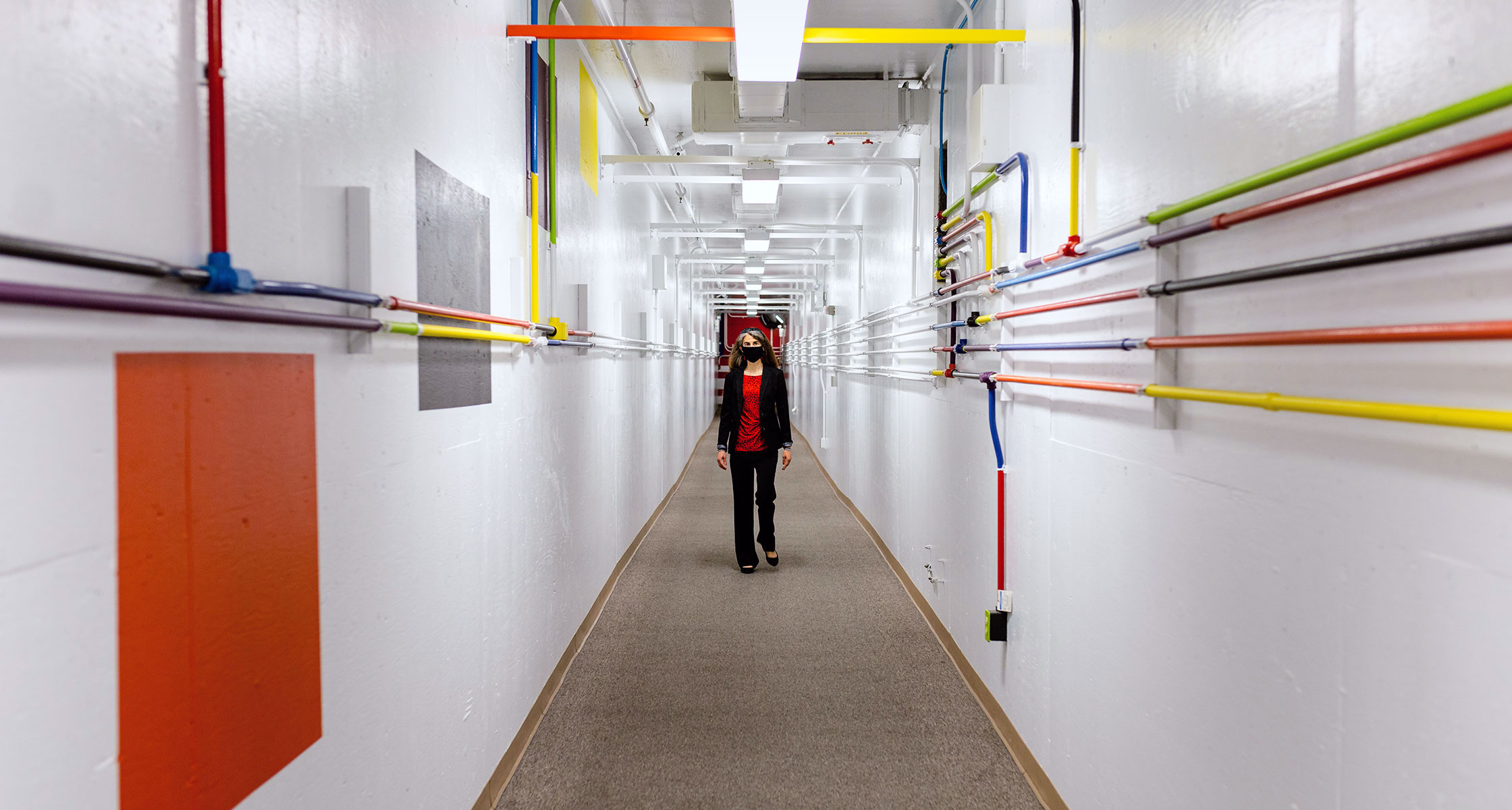A woman walks down a white corridor with colorful pipes running down the walls.