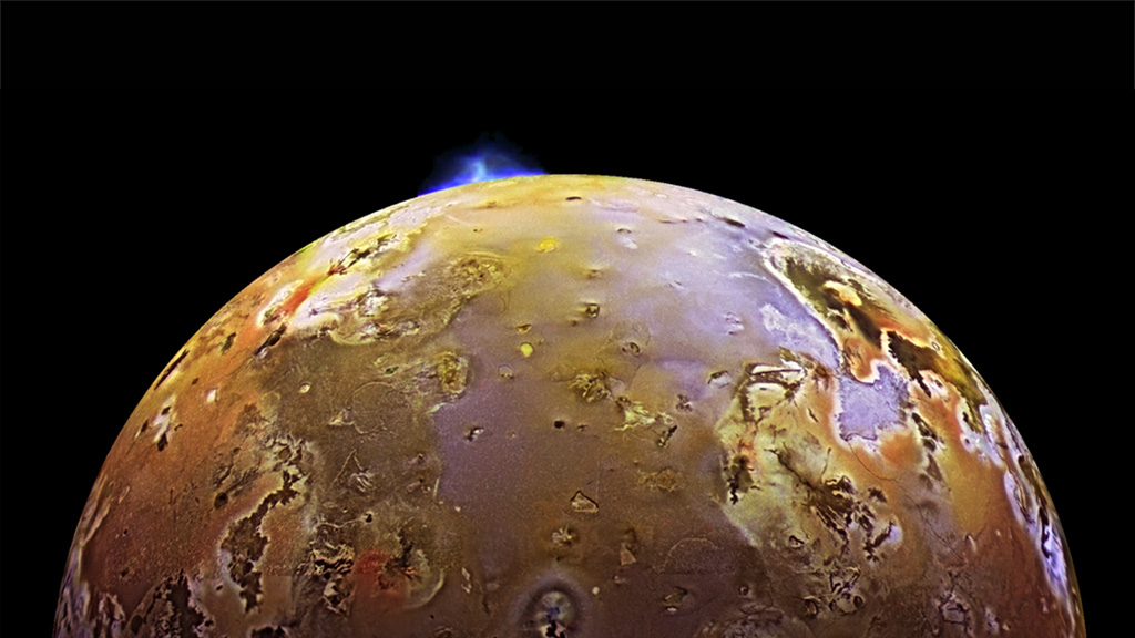 A yellow moon of Jupiter with a blue eruption.