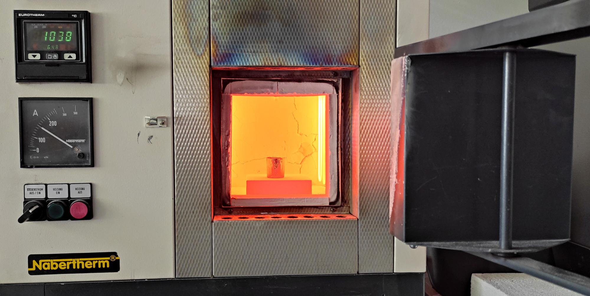 A laboratory oven glowing orange.