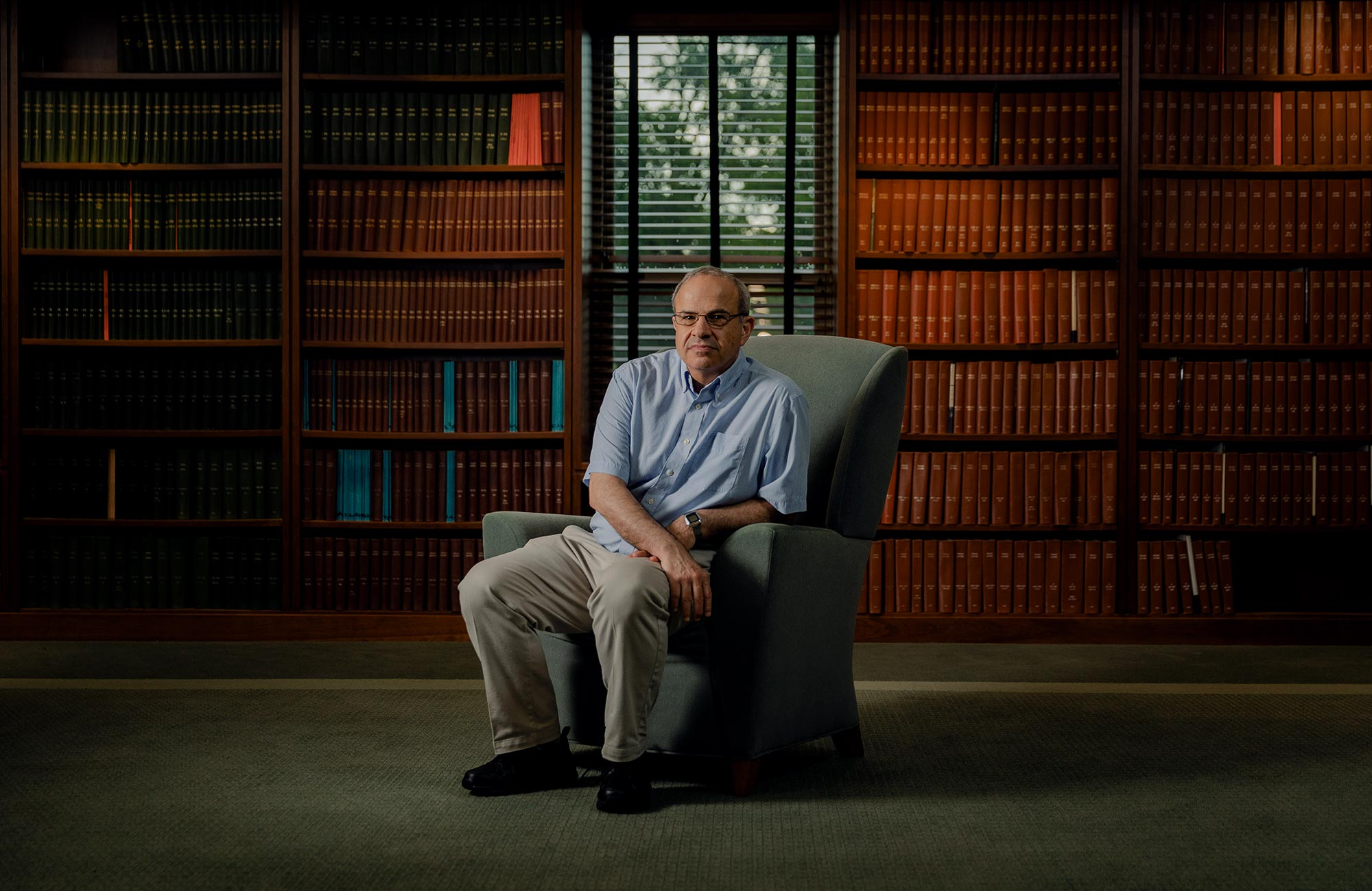 Color photo of Seiberg sitting in an easy chair in front of multiple shelves full of books.