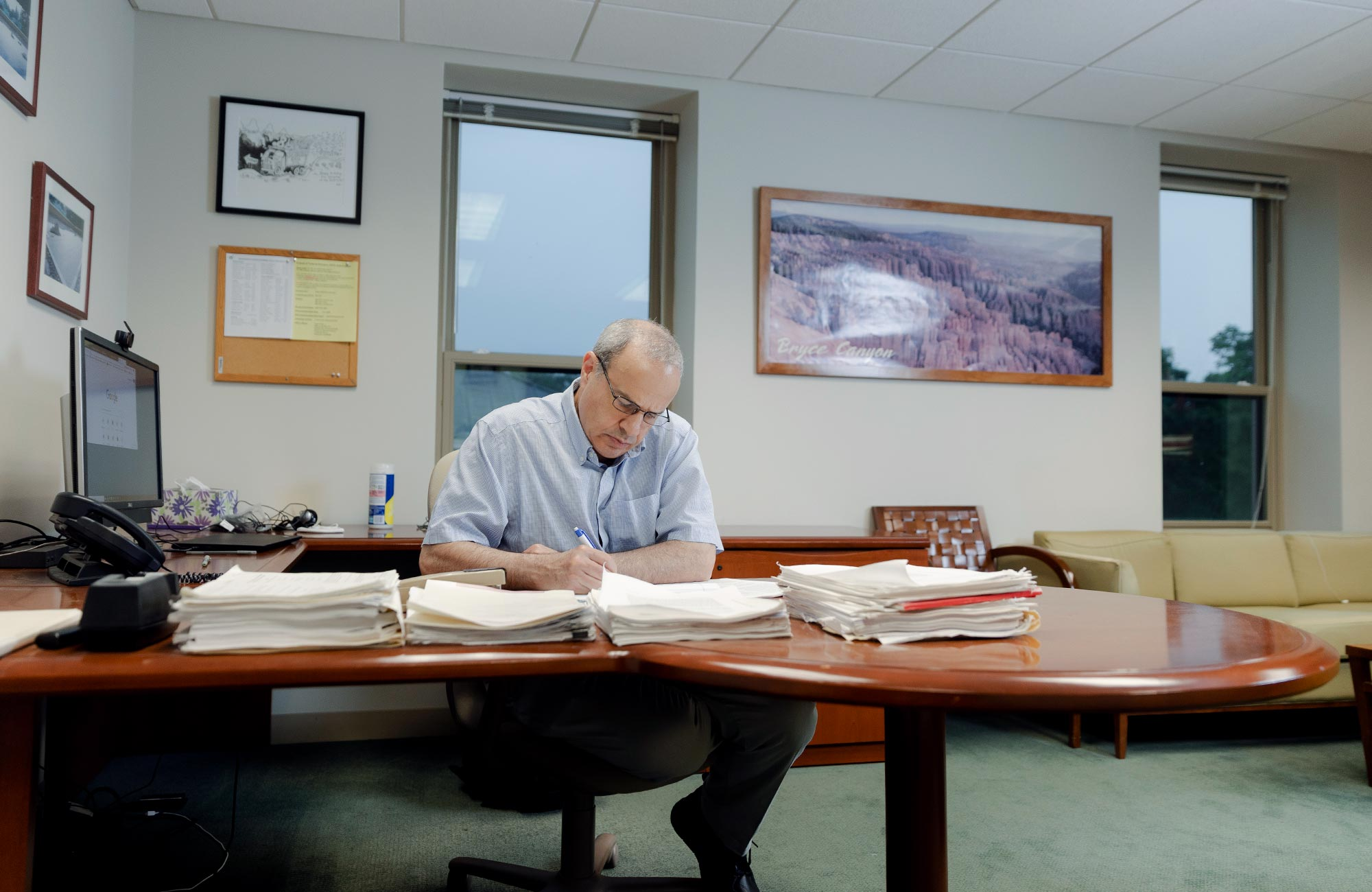 Color photo of Seiberg writing at the desk in his office