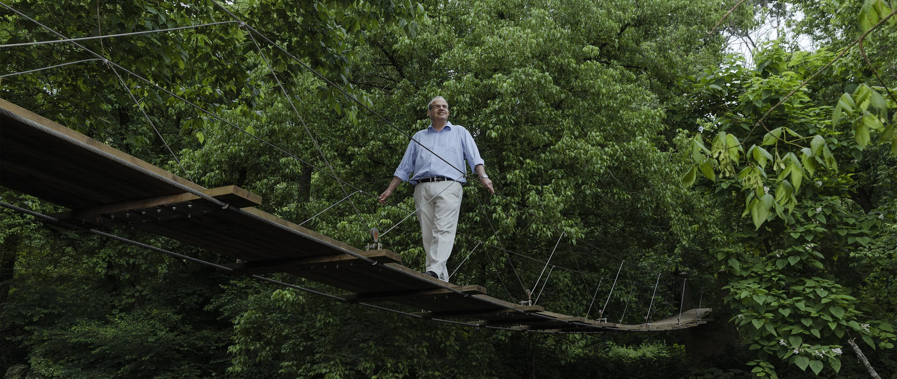 Color photo of Nathan Seiberg crossing a small wooden bridge in the woods.