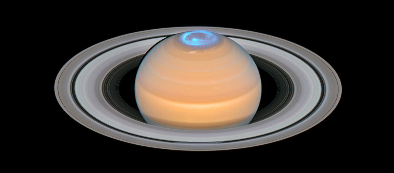 Saturn with glowing blue auroras.
