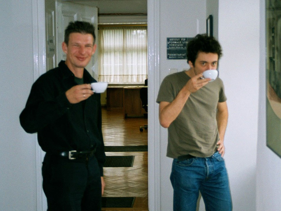 Two men standing up and drinking from coffee cups.