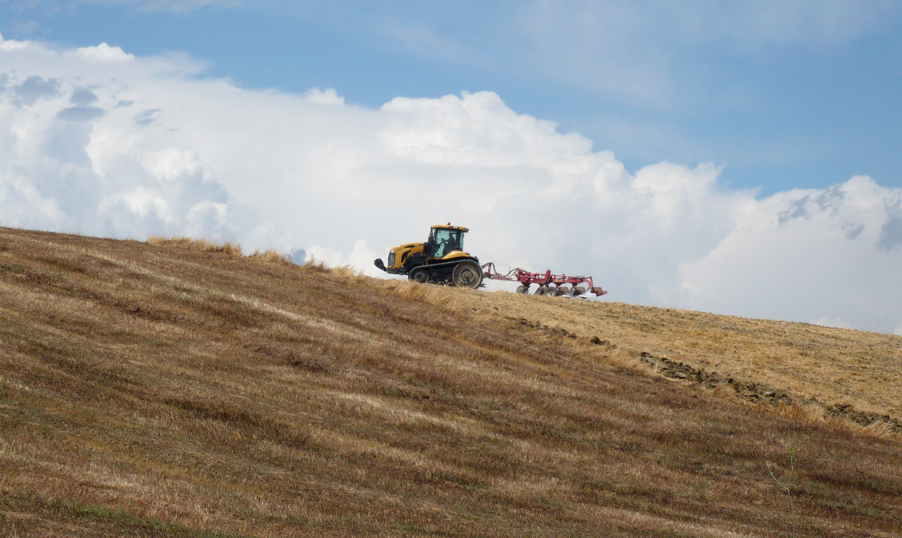 A tractor and a plow on a brown field.