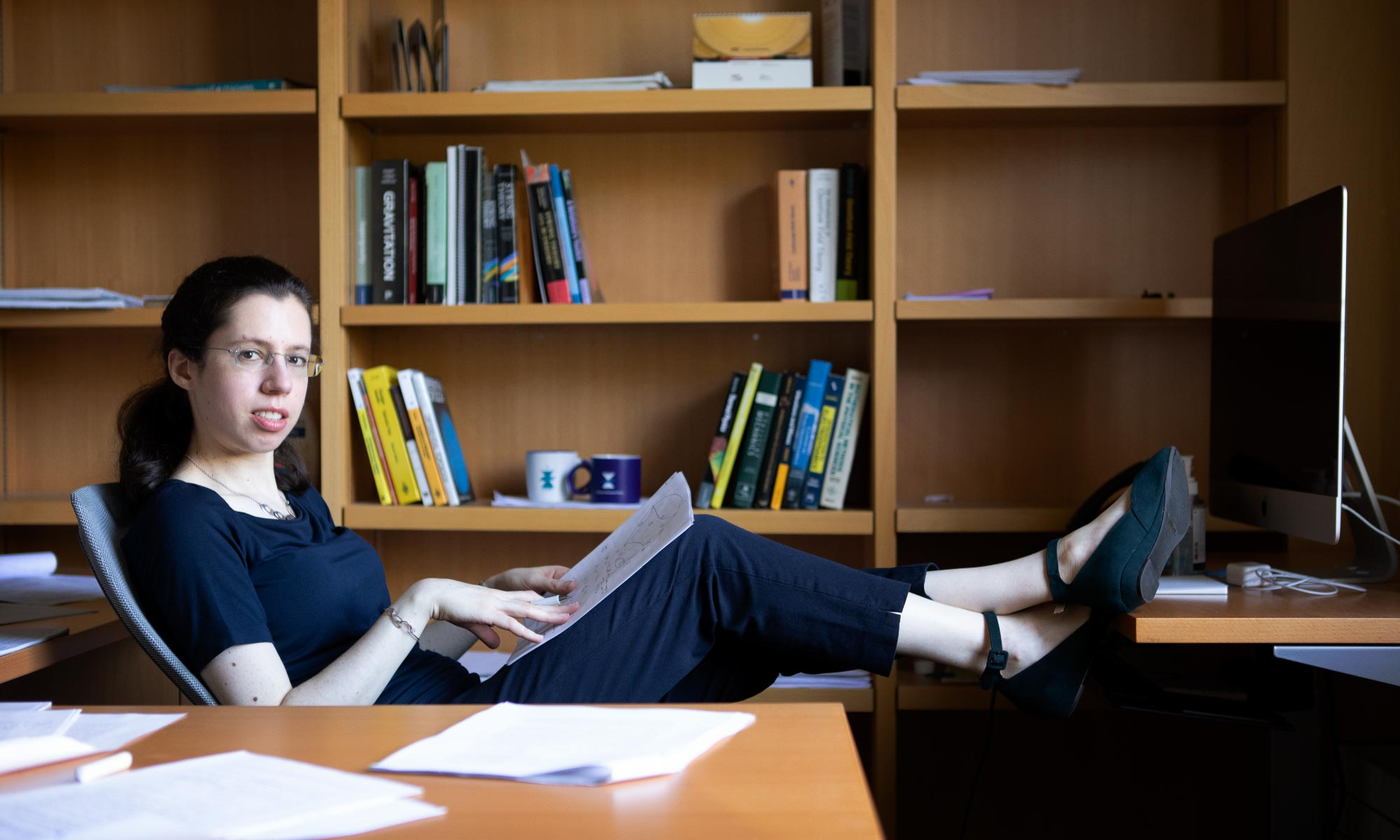 Photo of Engelhardt with her feet up on her desk glancing sideways at the camera with bookcases lining the wall behind.