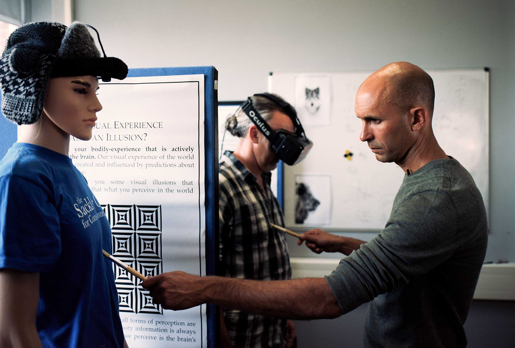 Seth touches a mannequin and a volunteer wearing a virtual reality headset.