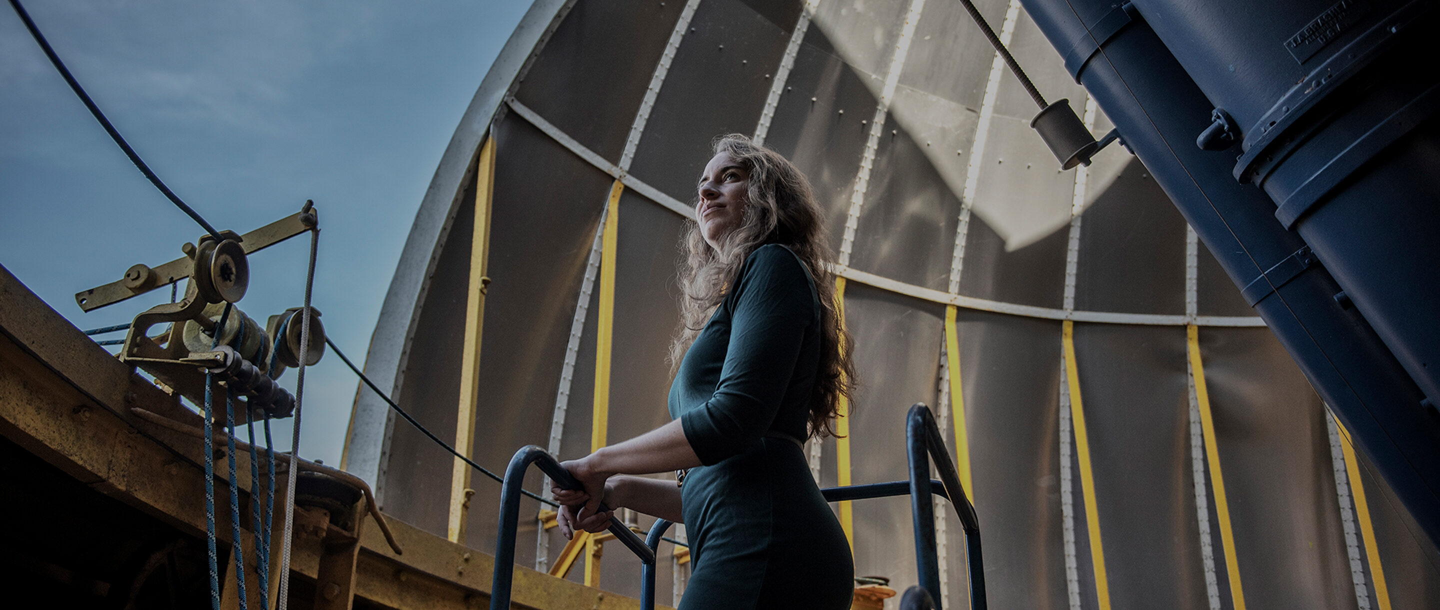 Kreidberg standing inside the dome of an observatory. Two tubes of a dual refractor telescope point through an opening in the dome.