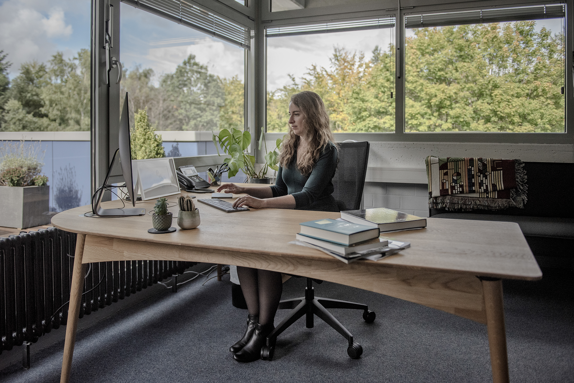 Kreidberg sits at a desk surrounded by glass walls that look out onto trees.